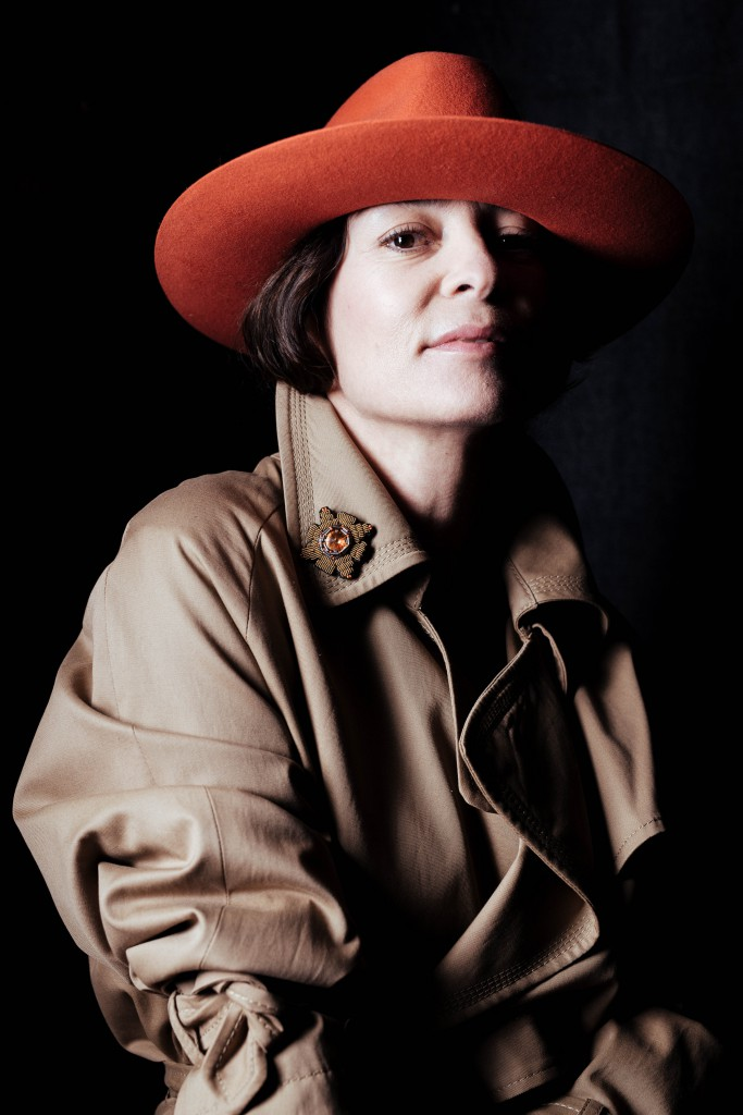 A brooch originally intended to embellish a fedora is affixed to the lapel of a trench coat