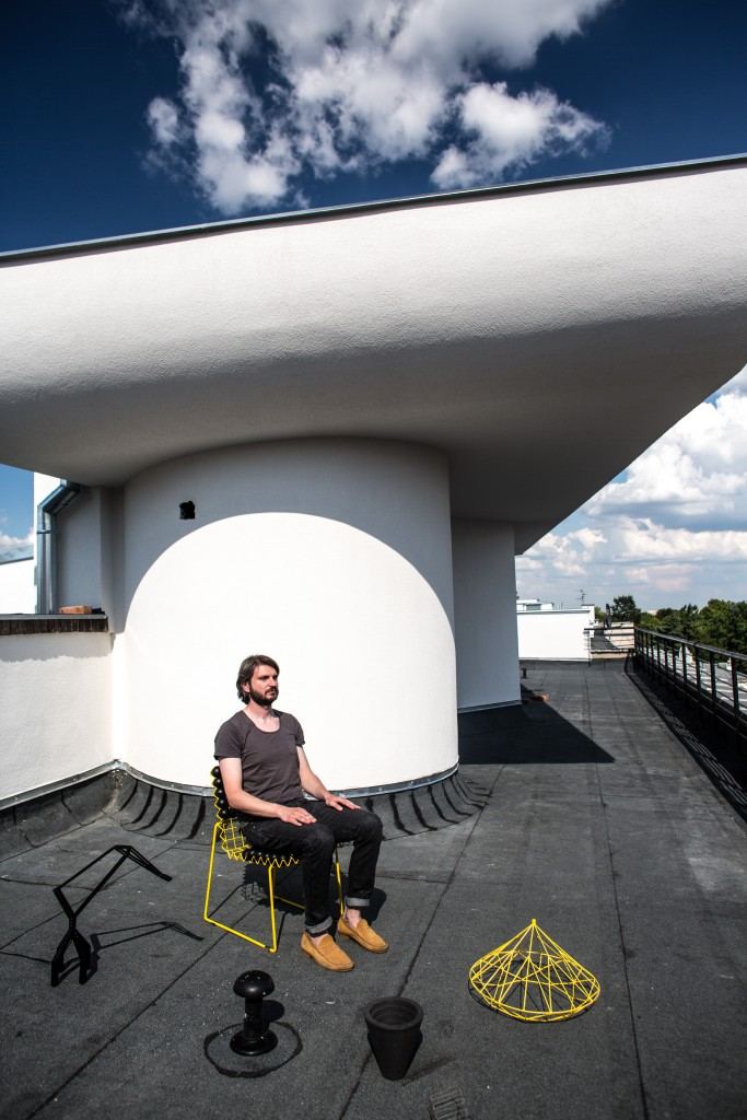 The designer sitting on the roof of his Warsaw studio with a range of his most recent works