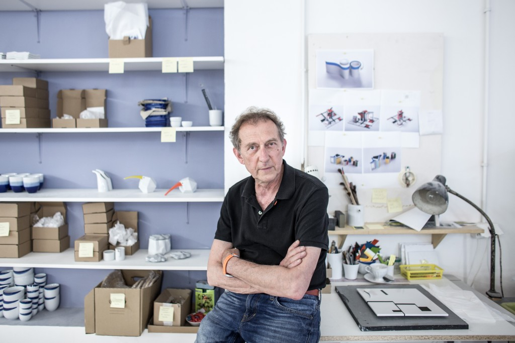 The designer sitting in front of his desk and display shelve