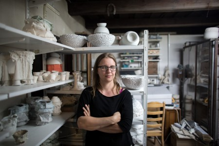 The designer in her Warsaw ceramic atelier, next to recent and older works