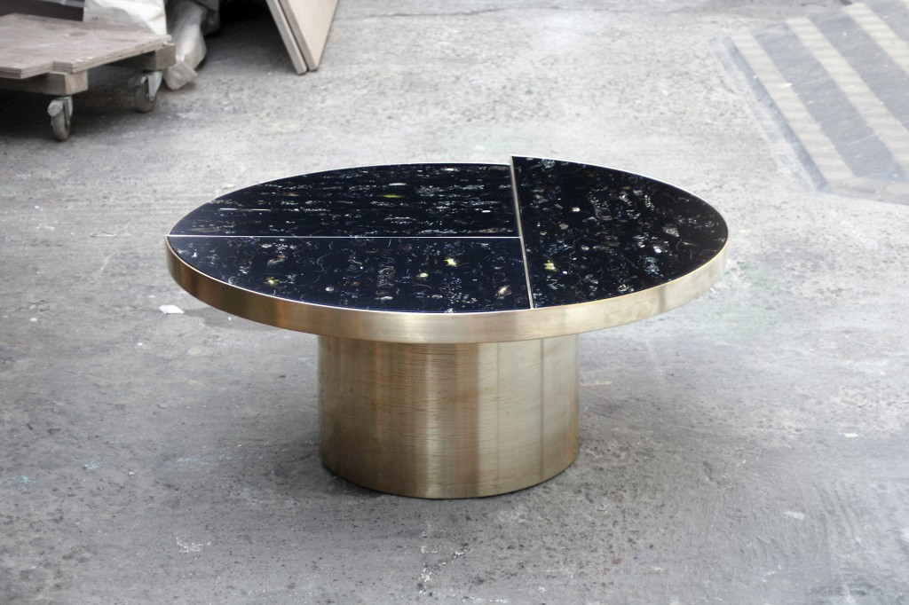 Flora table by Marcin Rusak, suspends flowers in black resin to create a marble-like material.