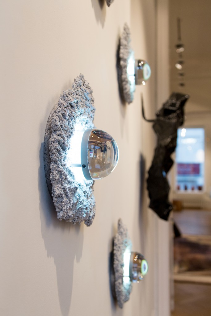 Wall installation of five Caviar sconces by Chen Chen and Kai Williams, silver shots, illuminated glass lens, 2017, in collaboration with Patrick Parrish Gallery, New York.