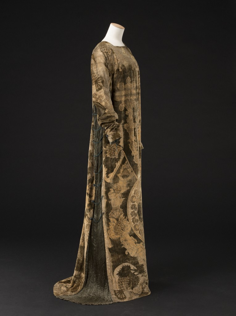Mariano Fortuny (1871-1949). Eleonora dress, golden printed green silk velvet, pleated green silk taffeta, green silk cords, black and white glass beads, golden silk taffeta lining, circa 1912. Collection Palais Galliera © Stéphane Piera / Galliera / Roger-Viollet